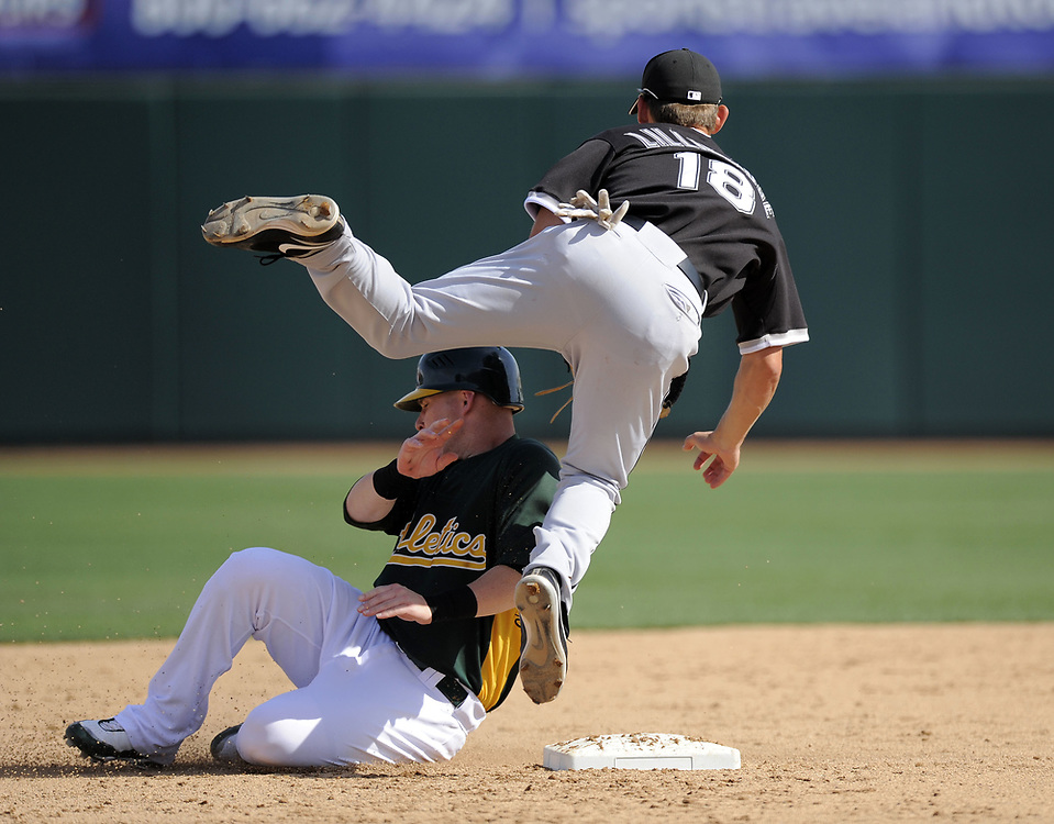 PHOENIX, AZ - MARCH 4:  Brent Lillibridge #18 of the Chicago White Sox drops the ball as Darik Barton #10 slides into Lillibridge during the game against the Oakland Athletics on March 4, 2009 at Phoenix Municipal Stadium in Phoenix, Arizona. Barton was called out on the play. (Photo by Ron Vesely)