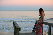 Red head woman in long flowered dress on steps to Jekyll Island beach at sunrise, sunset