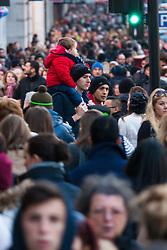 London, December 6th 2014. Tens of thousands throng the streets of London as shoppers take advantages of ongoing deals and discounts offered by retailers in the run-up to Christmas. PICTURED: A child rides on the shoulders of an adult, safe from the jostling crowds.