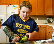 Zachary Frantzen helps prepare dinner in Longmont, Colorado July 19, 2010.  Zachary, 10, is in the Shapedown Program which is part of the child and teen weight management program at The Children's Hospital in Aurora. REUTERS/Rick Wilking (UNITED STATES)