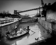 Couple in sampan try to pull a heavy piece of crumpled metal from a canal for salvage, while untreated waste water flows into the canal from a cement factory  near Xianfeng Er Cun, Shanghai, China.
