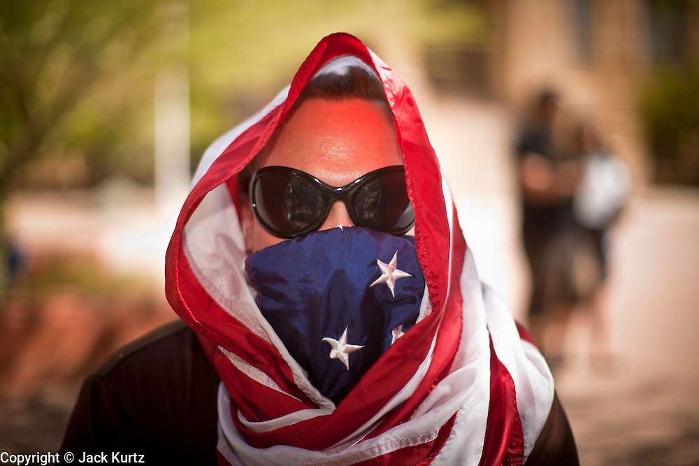 "22 OCTOBER 2011 - PHOENIX, AZ:    An Occupy Phoenix with his head wrapped in an American flag at Cesar Chavez Plaza in downtown Saturday. The demonstrations at Occupy Phoenix, AZ, entered their second week Saturday. About 50 people are staying in Cesar Chavez Plaza, in the heart of downtown. The crowd grows in the evening and on weekends. Protesters have coordinated their actions with police and have gotten permission from the city to set up shade shelters and sleep in the park, but without tents or sleeping bags, which is considered ""urban camping,"" instead protesters are sleeping on the sidewalk. PHOTO BY JACK KURTZ"