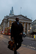 A black City worker walks past the neo-Roman pillars of Royal Exchange on 9th February 2017, in the City of London, England.
