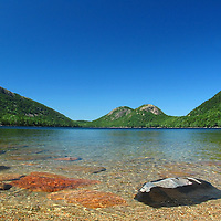 Picture perfect of Jordan Pond in the summer month of August. This waterscape is in the heart of Acadia National Park on Mount Desert Island and one of the best photo location for landscape photography. The shore line and rocks in the foreground provide interesting elements for a pleasing composition while the South and North Bubbles in the background are iconic photo subjects. Since the 1800's, people have come here for popovers and this picturesque view of the bubbles. <br />