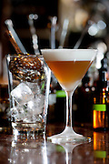 Beverage specialties created by the talented bartenders at Peche Restaurant and Bar, Austin, Texas. Fig Manhattan with foam topping next to a glass with  a straining spoon sitting on top of ice cubes.