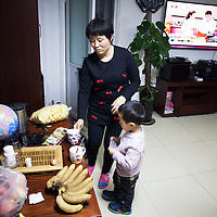 Beijing, March 11 : Cui Xinying helps her youngest son, Tian Ye in the kitchen while her eldest son, Tian Peng, 15, lies in the sofa.<br /> As a baby Tian Peng fell ill with brain   hemorrhage supposedly due to a lack of vitamin K. When Tian Peng was a kid, friends advised the parents to simply abandon him as there's neither enough help nor support in China apart from a small NGO. Tian is unable to speak, think, walk and needs help for everything.<br /> Chinese attitudes towards people with disabilities have improved in recent years, but the support of society and opportunities in education and employment are scarce.