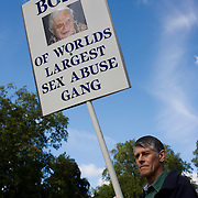 Protesters gather in Hyde Park to voice opposition to Catholic thinking during Pope Benedict XVI's papal tour of Britain 2010, the first visit by a pontiff since 1982. The man calls the Pope the head of a group of people responsible ox sex abusers and the face of Pope Ratzinger looking demonic is on his placard. Taxpayers footed the £10m bill for non-religious elements, which largely angered a nation still reeling from the financial crisis. Pope Benedict XVI is the head of the biggest Christian denomination in the world, some one billion Roman Catholics, or one in six people. In Britain there are about five million Catholics but only a quarter of Catholics regularly attend Sunday Mass and some churches have closed owing to spending cuts.