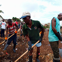 With the support of Save the Children, Kroo Bay residents clean the garbage off the river that crosses the slum before reinforcing the banks, Kroo Bay, Freetown, Sierra Leone.