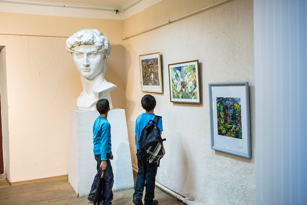 Two boys look at a copy of the head of Michelangelo's David statue on Monday, November 11, 2013 in Asbest, Russia.