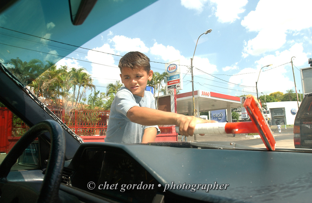 ASUNCION, PARAGUAY. Young Paraguayan street boy cleans a windshield in Asuncion, Paraguay on Thursday morning, March 16, 2006. Hundreds of street children, some as young as 4 years old and their parents, work the diesel fumed streets of the capital city by squeegeeing windshields, panhandling and selling various items to drivers.