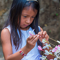 PANCHIMALCO , EL SALVADOR - MAY 08 : A Salvadoran girl decorates palm fronds with flowers during the Flower & Palm Festival in Panchimalco, El Salvador on May 08 2016