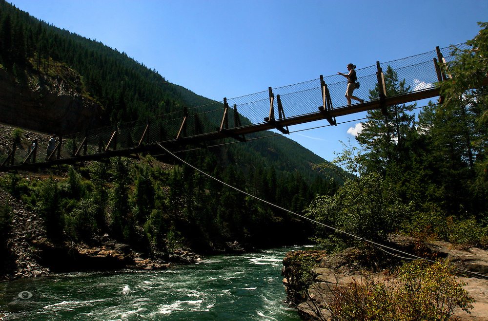 A visitor makes their way across a rope bridge strung across the fast moving Flathead River about Glacier National Park.