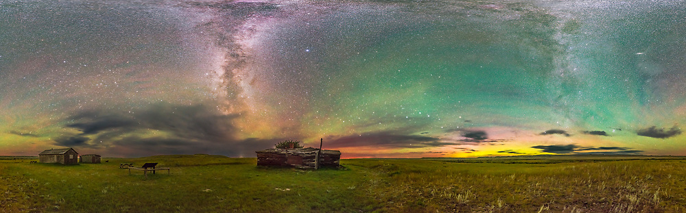 A 360&deg; panorama of the entire sky over the historic and pioneer Larson Ranch site in the Frenchman River Valley in Grasslands National Park, Saskatchewan, Canada. Grasslands in a Dark Sky Preserve and from most of the Park no lights at all can be seen and none light the sky. This is the natural sky, complete with colourful sky glows. <br /> <br /> The clouds here look dark, silhouettted against at sky lit only by natural sources: the stars, the Milky Way, the aurora at right, and a general airglow tinting the sky green to the north at right, with some red bands of airglow at left to the south. All ground illumination here is from these natural night light sources.<br /> <br /> The Milky Way was arching overhead when I shot this, so in this &ldquo;equirectangular&rdquo; projection it stretches up from the south at left of centre and spreads out across the top of the frame then descends to the northeast at right. The Pleiades is rising at lower right and at upper right is the Andromeda Galaxy. The Big Dipper is just right of centre low on the northern horizon. From this latitude of 49&deg; N the Big Dipper is circumpolar. <br /> <br /> This is a stitch of 32 panels, shot with the iOptron iPano motorized panning mount, each panel being 40 seconds at f/2.8 with the Sigma 24mm lens and Nikon D750 at ISO 6400. Overlap was 35%. Stitched with PTGui.