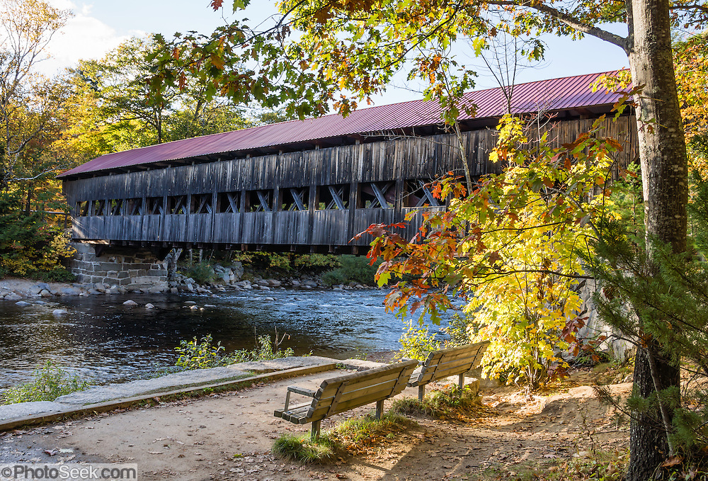 """Albany Covered Bridge was built in 1858 and renovated in 1970 in the town of Albany in White Mountain National Forest, New Hampshire, USA. Albany Covered Bridge spans the Swift River along Passaconaway Road just east of Kancamagus Highway (NH Route 112), six miles west of Conway. Come around the first week of October to enjoy leaf peeping during the peak of autumn foliage colors. In order to reach Covered Bridge Campground, the 7' 9"""" height restriction of Albany Covered Bridge requires larger RVs to loop around via Conway on Kancamagus Highway (NH Route 112), go left (east) on H113, go left (north) on Washington Street, fork left on West Side Road, then go left (west) on Passaconaway Road for six miles to the nice National Forest campground near the covered bridge. The White Mountains (a range in the northern Appalachian Mountains) cover a quarter of the state of New Hampshire."""