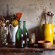 While wandering around a New York City building, I came across this shelf. The light from the window was all I could hope for. A still life of dried flower arrangements, baskets, pitchers, and two empty green wine bottles sitting on a wooden shelf hanging on a concrete wall.