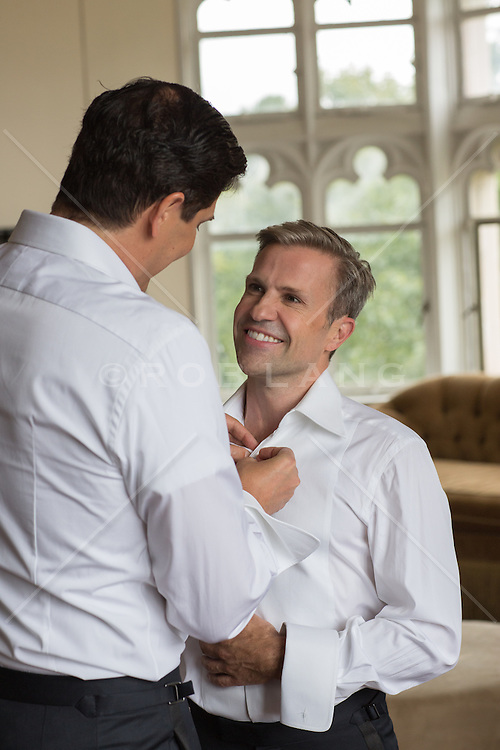 gay man helping his partner dress for their wedding