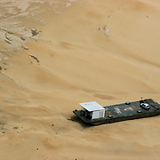 Oct. 22, 2005. Amazon (Brasil). Documentation of a very bad drought on the Amazon region. Barge with a car sitting on a sand bank on the Solimoes river between Tefe and Mamiraua lake..©Daniel Beltra/Greenpeace