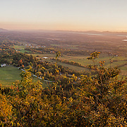See the sun set over the Adirondacks from atop Mount Philo State Park (established 1924), in Charlotte, Vermont, USA. From atop Mount Philo (968 feet elevation), see Lake Champlain and the Adirondack Mountains to the west and the Green Mountains to the east and south. Ascend via steep narrow car road (not suitable for RVs longer than 25 feet) or by trail. Mt. Philo is comprised of hard sedimentary rocks (Cambrian Monkton Quartzites) that are thrust over younger Ordovician rocks of the Stony Point Formation. Its Cambrian rocks were deposited 500 million years ago on a warm shallow marine shelf along the east coast of Laurentia (Proto North America) then tectonically uplifted. The panorama was stitched from 16 overlapping photos.