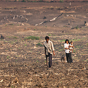 A Cambodian landmine victim and his family make their way through a recently plowed field near Pailin, Cambodia, along the border with Thailand.