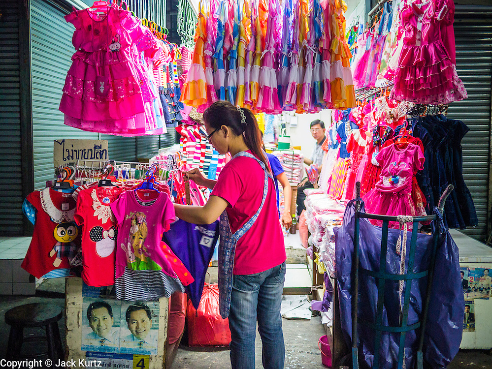 30 MAY 2013 - BANGKOK, THAILAND:   A woman sets up her clothing stall at Bobae Market in Bangkok. Bobae Market is a 30 year old famous for fashion wholesale and is now very popular with exporters from around the world. Bobae Tower is next to the market and  advertises itself as having 1,300 stalls under one roof and claims to be the largest garment wholesale center in Thailand.   PHOTO BY JACK KURTZ