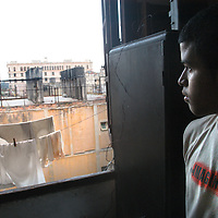 A young man looks out the window of his family's apartment in Havana.