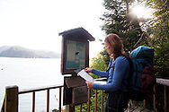 Stephanie Haynes signs in at the logbook before beginning a hike on the Saddle and Alpine Ridge trail in Kachemak Bay State Park, near Homer, Alaska.