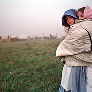 Jessica Hodson left, age 9 and her sister Melissa, age 9, both of Ann Arbor, Michigan try to stay warm by sharing the same coat in the early morning fog as the wagon train gets ready to leave on the third day. They were taking part in a re-inactment of the original crossing of the plains by early Mormon pioneers enroute to Salt Lake City, Utah. This photo was taken west of Omaha, Nebraska April, 29, 1997. Photo by August Miller