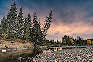 A scene at the Allen Bill Pond area along Highway 66 and on the Elbow River in Kananaskis Country, of trees along the eroded banks of the river still showing some of the devastation from the floods of June 2013. The scene is lit by moonlight from a gibbous Moon, while light pollution from Calgary to the east discolours the clouds, but adds a &ldquo;nice&rdquo; tonal value to the sky. <br /> <br /> This is a stack of 5 exposures: one for the sky to keep the stars as points, and four for the ground, median combined, to smooth noise. All were 30 second exposures at f/5.6 with the 24mm lens and Nikon D750 at ISO 800.