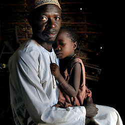 Quss M. Bani holds his niece Fatima Musa, 7, in their village of Mnolela, Tanzania. Fatima saw her mother Somoe Linyambe, 40, get killed and eaten by a lion when she was 5 years old in the village of Nachunyu and told her uncle that a cow had taken her because she had no idea what a lion was.