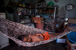 A Vietnamese boy naps in a hammock at noon inside a house-store, Ninh Thuan Province, Vietnam, Southeast Asia