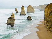 "Twelve Apostles Marine National Park protects several collections of miocene limestone sea stacks in the Indian Ocean (or Southern Ocean according to Australian geographers) offshore of Port Campbell National Park, along the Great Ocean Road, Victoria, Australia. Known as the ""Sow and Piglets"" until 1922, the pictured set of sea stacks was renamed to ""The Apostles"" then to Twelve Apostles for tourism, despite only having nine sea stacks (2004 photo). Eight stacks remained after the one at left collapsed in 2005. The Great Ocean Road (B100) is a 243-km road along the southeast coast of Australia between Torquay and Warrnambool, in the state of Victoria. Dedicated to casualties of World War I, the Great Ocean Road was built by returned soldiers between 1919 and 1932 and is the world's largest war memorial."