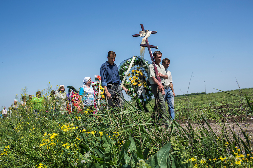 STAROVARVAROVKA, UKRAINE - MAY 16:  Mourners process with the casket of Elena Ott, 42, from her family's house to a local cemetery on May 16, 2014 in Starovarvarovka, Ukraine. Ott was killed two days prior when the car she was riding in was fired on by forces her family believes to be the Ukrainian military. (Photo by Brendan Hoffman/Getty Images) *** Local Caption ***