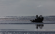 Bird watcher on airboat scans horizon for birds on Copper River Delta in Southcentral Alaska. Spring. Morning.