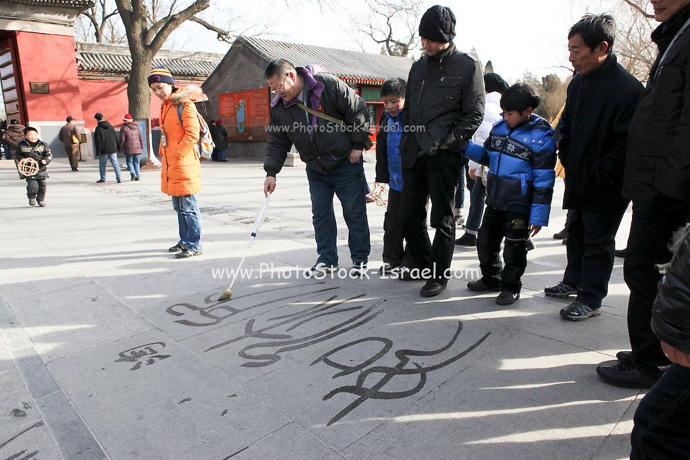 China, Beijing, Summer Palace built by Empress Cixi. Visitors use the wide open spaces to practise their calligraphy with home made water based writing sticks
