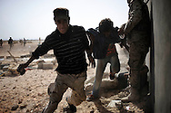 LIBYAN ARAB JAMAHIRIYA : Libyan rebel fighters run away from an unexploded missile landed close to them after the explosion of the  forces loyal to Moamer Kadhafi's ammunition deposit  in Um al Far, on July 28, 2011.ALESSIO ROMENZI