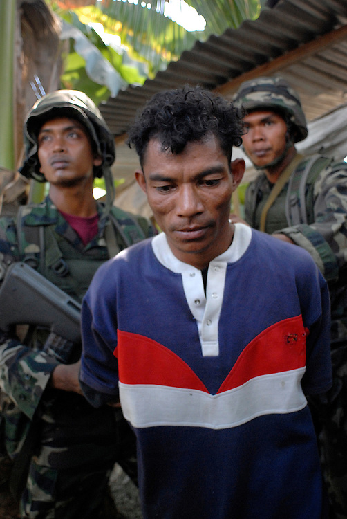 Malaysian troops detain a suspected gang member after a clash between rival gangs near the bridge at Comoro, Dili. East Timor 04/06/06