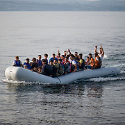 A small inflatable boat with more than 40 Afghan refugees,minutes before landing on the beach of Skala Sykaminias, Lesbos island, Greece. The people onboard singing with joy before their arrival to Europe. Everyday hundreds of refugees, mainly from Syria and Afghanistan, are crossing in small overcrowded inflatable boats the 6 mile channel from the Turkish coast to the island of Lesbos in Greece. Many spend their life savings, over $1000, to buy a space on those boats.