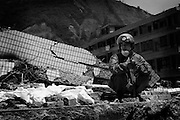 A Peoples Liberation Army worker takes a break from locating and recovering some of the thousands of bodies buried in the remians of buildings in Bichuan.