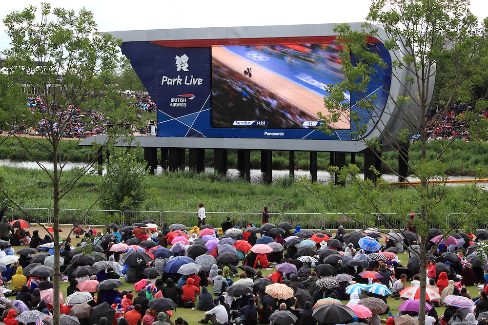 People watch a cycling event in the Park Live screens in the rain at the London 2012 Olympics