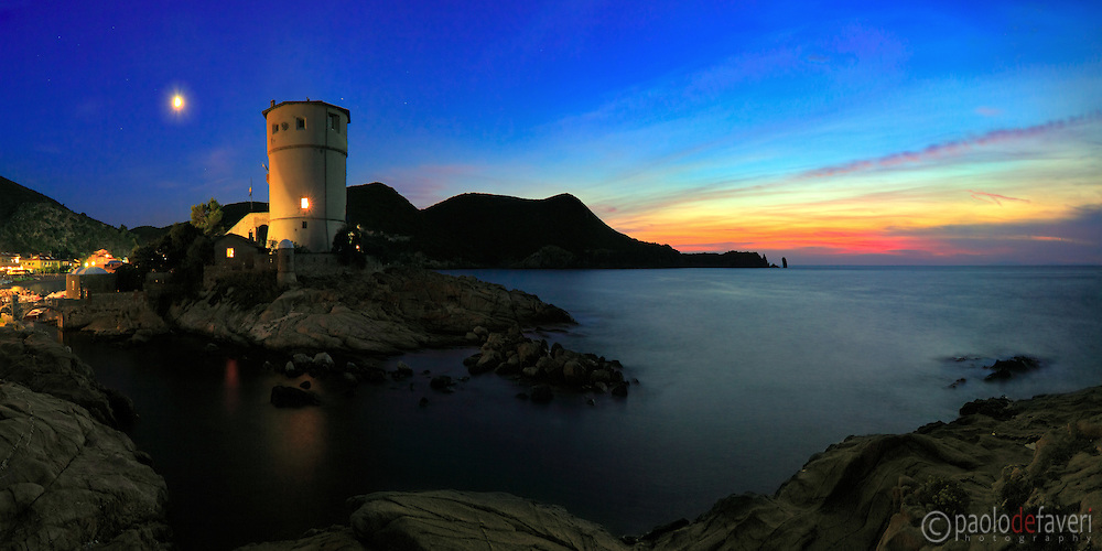 A twilight panoramic view of the tower of Campese at Isola del Giglio, a small wild island of the Tuscan Archipelago. It was built at the end of XVII century as a watchtower and a fortress, it was used to alert the population of possible sea invaders (pirates, that is ) and it was at that time armed with a dozen of cannons . At the present days it's been converted to a tourist resort and residence. This panorama is stitched from seven vertical frames.