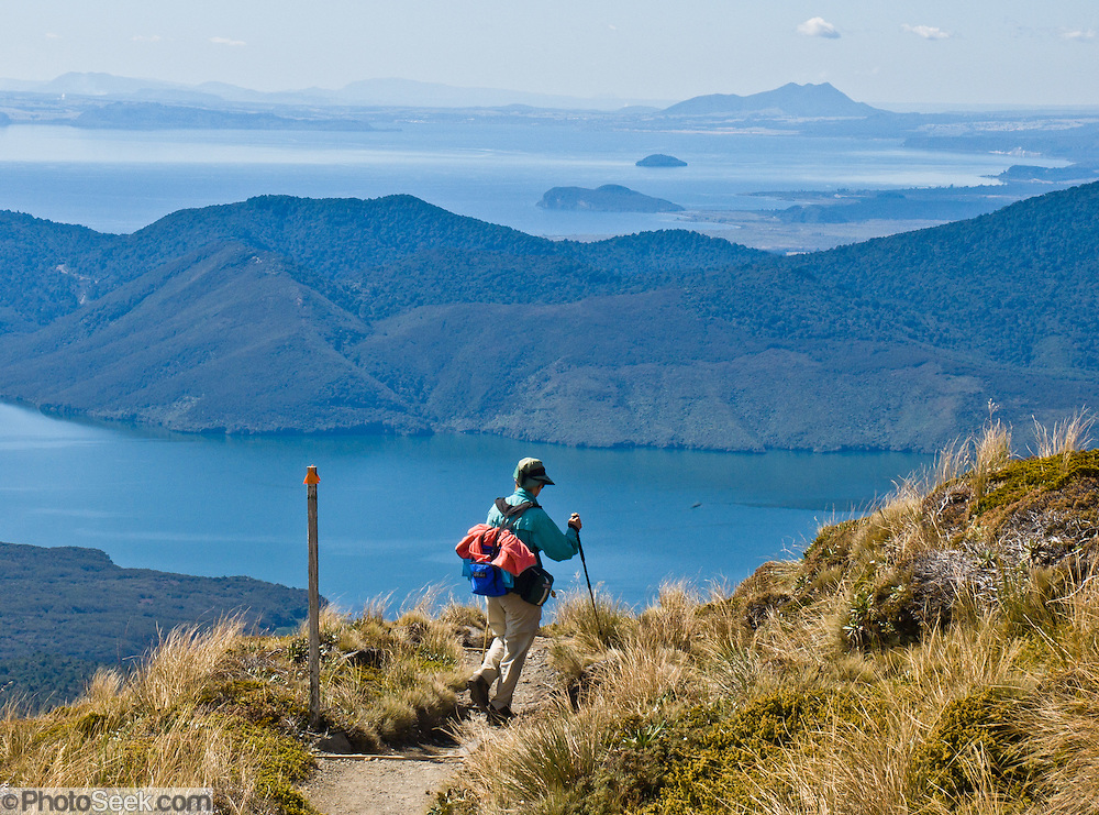 A tramper (hiker) views Lake Rotoaira and Lake Taupo (in the distance), from the Tongariro Crossing in Tongariro National Park, New Zealand, North Island. In 1990 and 1993, UNESCO honored Tongariro National Park as a World Heritage Area and Cultural Landscape.