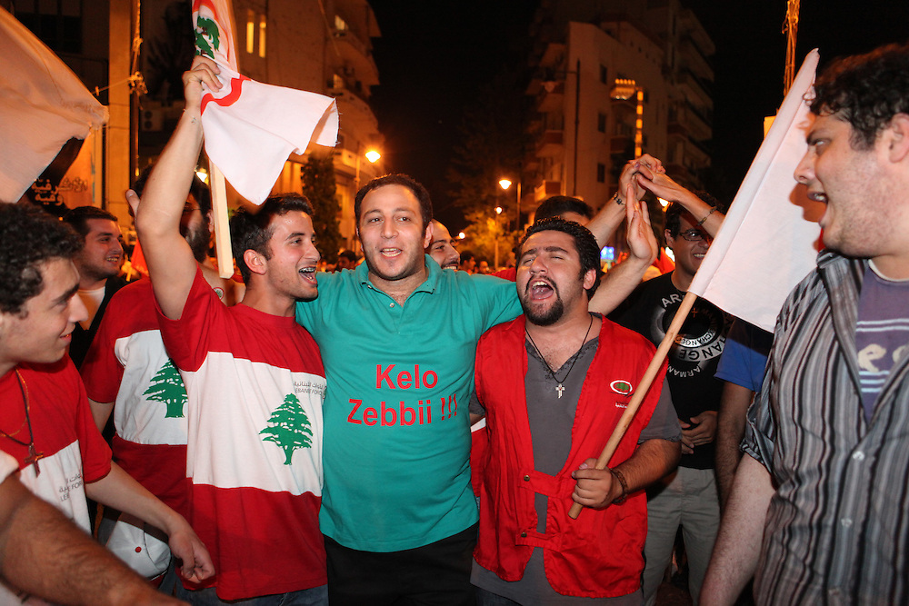 "As the results started to come out from Lebanon's general elections, the Beirut 1 district appeared to be swept by Christian groups from the pro-western ""March 14"" alliance. As exit polls projected the win for March 14, supporters of the Lebanese Forces and Phalange parties came out to the Ashrafiyeh neighborhood's Sassine Square to celebrate. At around 1am Nadim Gemayel made a suprise appearance and briefly addressed supporters. Nadim Gemayel is the son of the Phalange party founder, Pierre Gemayel. Nadim's father, Bashir was assasinated in 1982 during the Lebanese civil war and remains one of the most popular icons of many of the Lebanon's Maronite Christians. The 27-year-old Nadim Gemayel will be one of Lebanon's youngest parliamentarians. The celebrations at Sassine were one of Lebanon's first celebrations after the elections ended on 7 June.///March 14 alliance supporters celebrate their victory in the elections at Beirut's Sassine Square. The man in the middle wears a shirt that says ""Eat my dick"" in Arabic, directed towards the opposition coalition who lost in the June 7 elections."