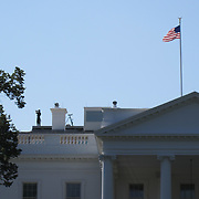 Secret Service Agent checking the skies from the roof of the White House in Washington, DC. Just before the President leaves by helicopter. Special moment!