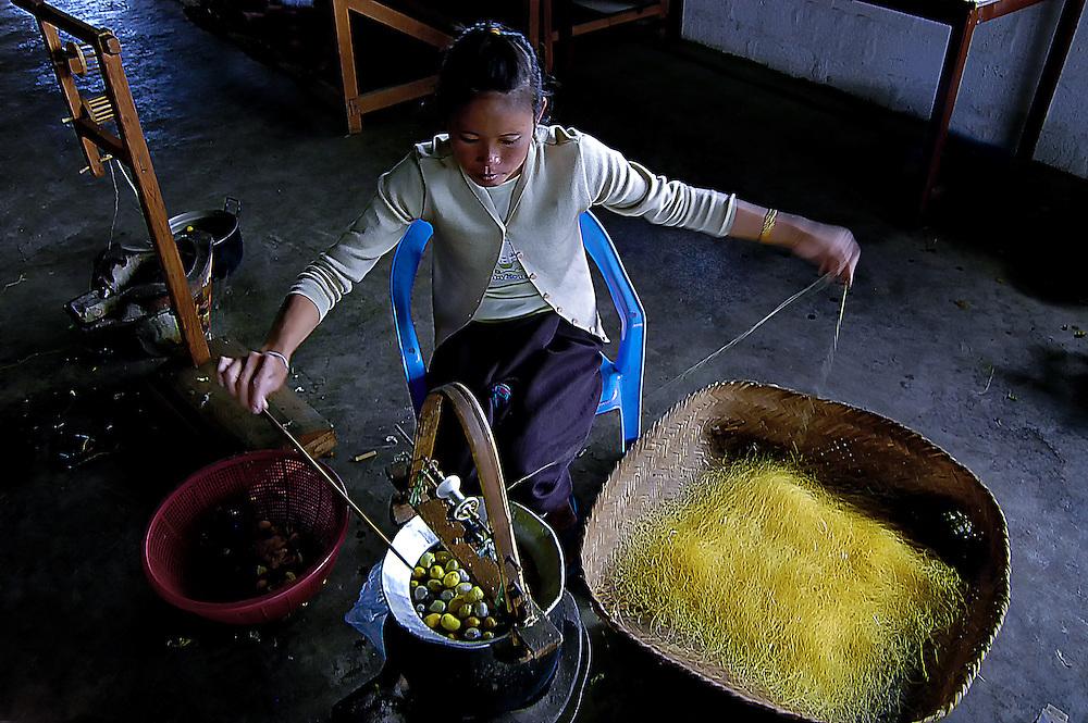 A woman spinning silk in Xieng Kuang, Laos.