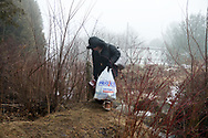 February 25, 2017-Hemmingford, Quebec : A woman from Sudan carries her belongings across the Canadian border on Roxham Road in southern Quebec.