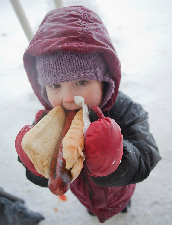 A young child is dressed warmly for winter and eats a hot dog as big as she is at the Winter Festival in Gustavus, AK. MR