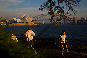 Sydney Sites travel series. The Sydney Skyline featuring the Opera House and the Harbour Bridge in the background as early morning runners jog around the Sydney landmark Mrs Macquaries Chair in Sydney Botanical gardens.