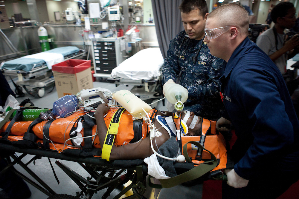 The first victim of the earthquake in Haiti, a  twenty year old man being treated for a brain injury, is wheeled into the casualty receiving area of the USNS Comfort, a naval hospital ship, after being flown by helicopter from the USS Vinson on Wednesday, January 20, 2010 in the Atlantic ocean near Port-Au-Prince, Haiti. The Comfort deployed from Baltimore, bringing nearly a thousand medical personnel to care for victims of Haiti's recent earthquake, and is expected to arrive off the coast of Port-Au-Prince on Wednesday.