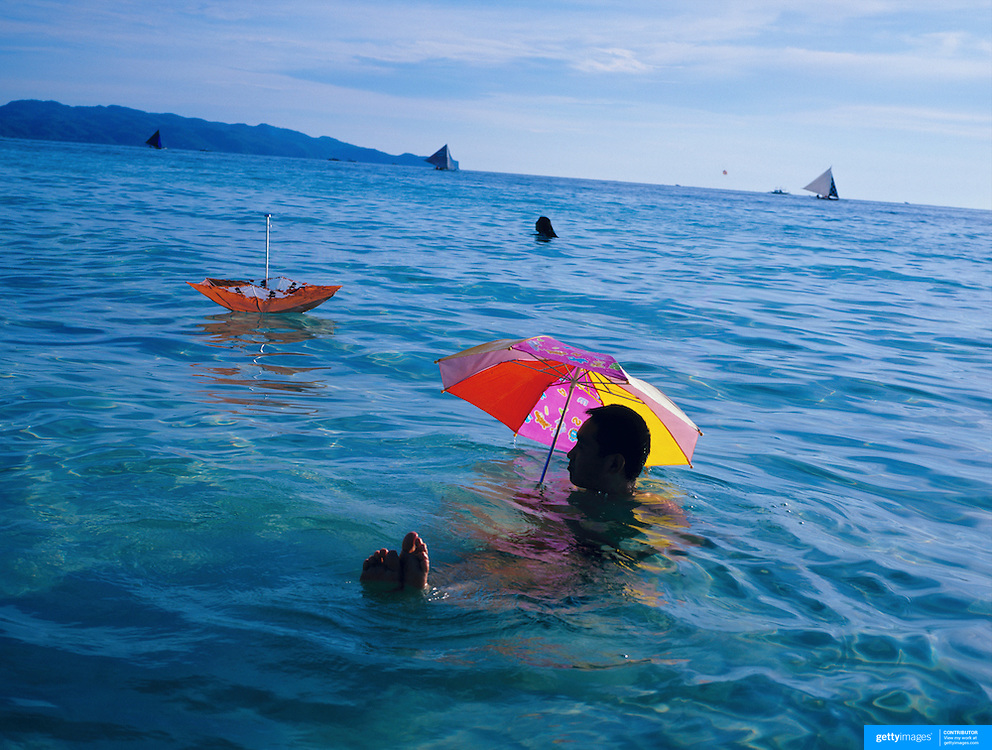 Asian tourist enjoy the pristine waters of White Beach while protecting themselves from the sun with umbrella's on Boracay Island, the Philippines on October 3, 2008, Photo Tim Clayton..Asian tourists at White Beach, Boracay Island, the Philippines...The 4 km stretch of White beach on Boracay Island, the Philippines has been honoured as the best leisure destination in Asia beating popular destinations such as Bali in Indonesia and Sanya in China in a recent survey conducted by an International Travel Magazine with 2.2 million viewers taking part in the online poll...Last year, close to 600,000 visitors visited Boracay with South Korea providing 128,909 visitors followed by Japan, 35,294, USA, 13,362 and China 12,720...A popular destination for South Korean divers and honeymooners, Boracay is now attracting crowds of tourists from mainland China who are arriving in ever increasing numbers. In Asia, China has already overtaken Japan to become the largest source of outland travelers...Boracay's main attraction is 4 km of pristine powder fine white sand and the crystal clear azure water making it a popular destination for Scuba diving with nearly 20 dive centers along White beach. The stretch of shady palm trees separate the beach from the line of hotels, restaurants, bars and cafes. It's pulsating nightlife with the friendly locals make it increasingly popular with the asian tourists...The Boracay sailing boats provide endless tourist entertainment, particularly during the amazing sunsets when the silhouetted sails provide picture postcard scenes along the shoreline...Boracay Island is situated an hours flight from Manila and it's close proximity to South Korea, China, Taiwan and Japan means it is a growing destination for Asian tourists... By 2010, the island of Boracay expects to have 1,000,000 visitors.