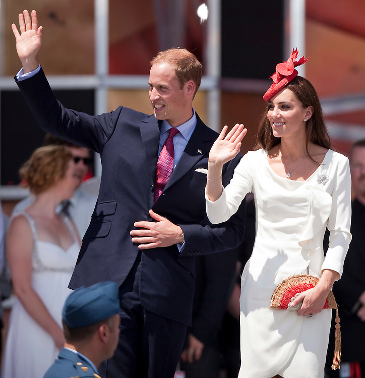 Britain's Prince William speaks with his wife Catherine the Duchess of Cambridge following his speech to hundreds of thousands who gathered to celebrate Canada Day on Parliament Hill in Ottawa, Canada,  July 1, 2011. The duke and Duchess are on a nine day tour of Canada, their first official foreign trip as husband and wife.<br /> <br /> AFP PHOTO/GEOFF ROBINS